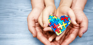 two pairs of hands holding a heart made of puzzle pieces